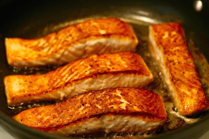 golden brown salmon fillets after turning them over
