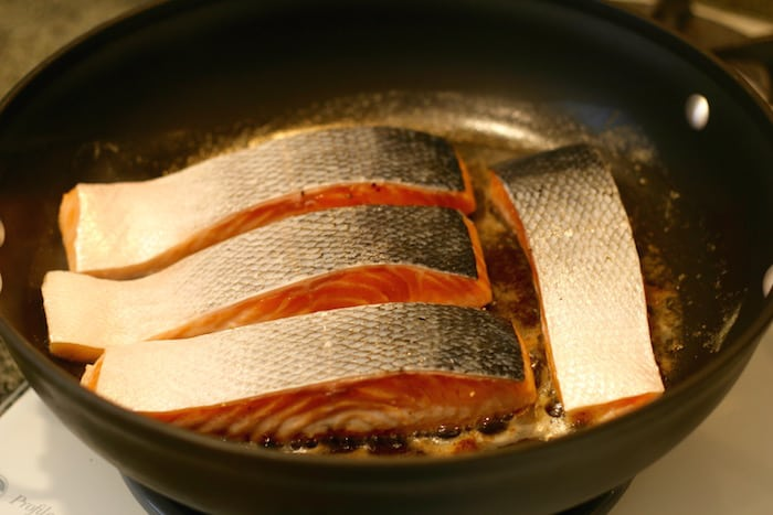 pan searing salmon fillets face down to start