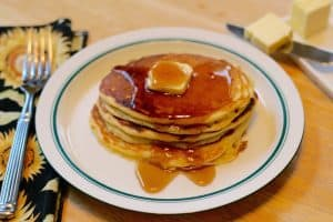 three or four Einkorn Flour pancakes served up on a plate with syrup