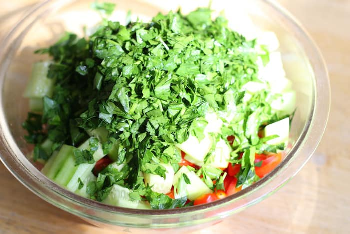 adding parsley to cucumber tomato salad