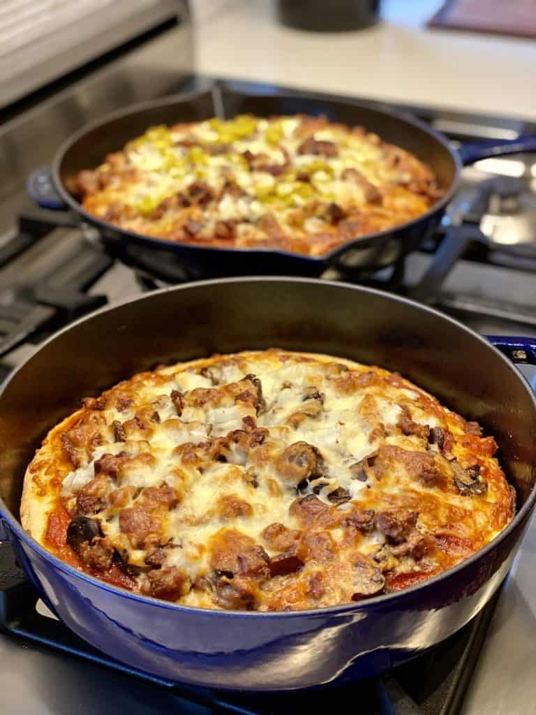 two pizzas made in enamel Staub pans