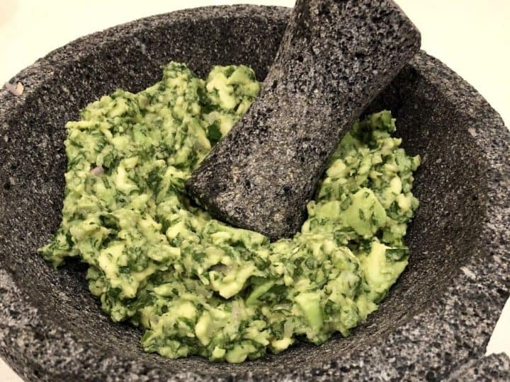 finished guacamole made from two avocados served in a stone molcajete