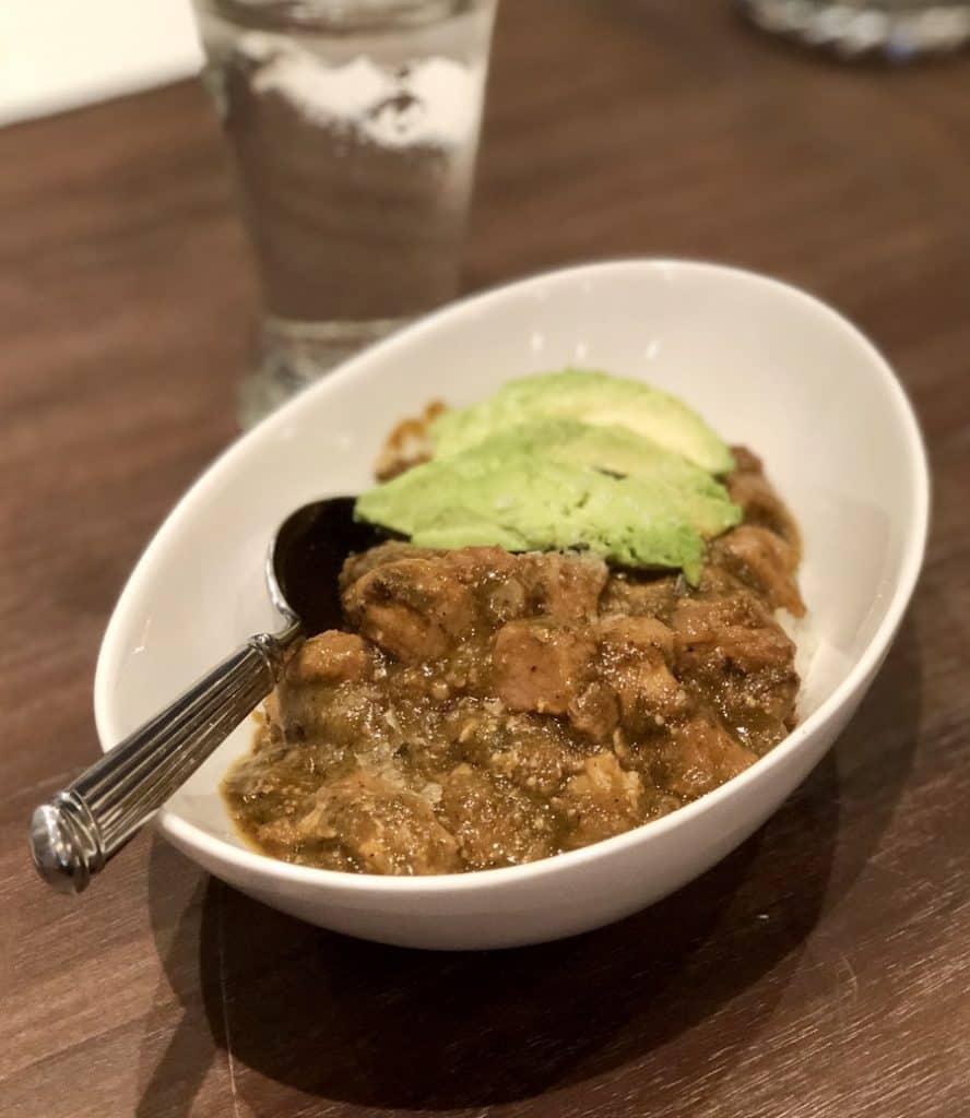 pork guisado or pork stew served with avocado