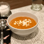 finished bowl of roasted carrot soup with a few goat cheese crumbles