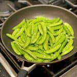 finishing sugar snap peas in pan with olive oil and salt